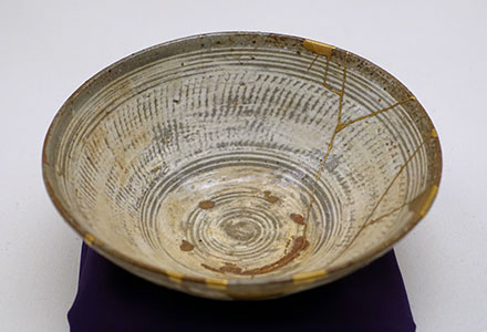 A ceramic bowl, broken and repaired with gold.